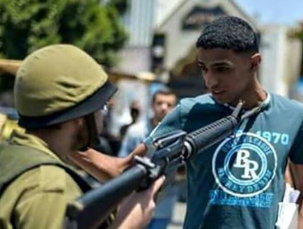 Staged photo of IDF soldier pointing rifle at a Palestinian youth